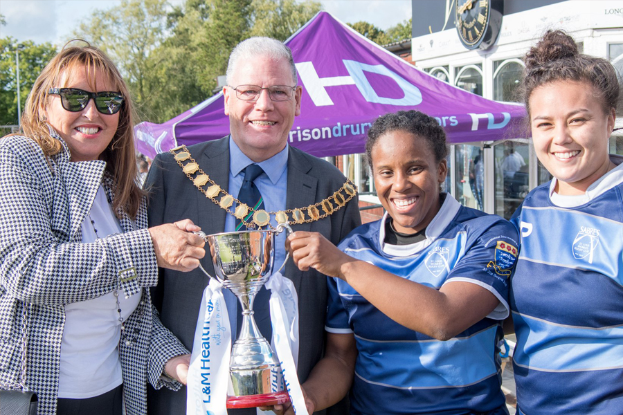 Jeanne Davies presented a trophy to the winning ladies team at Preston Grasshoppers Rugby Football Club International tournament